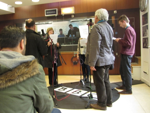 People standing in a circle facing microphones